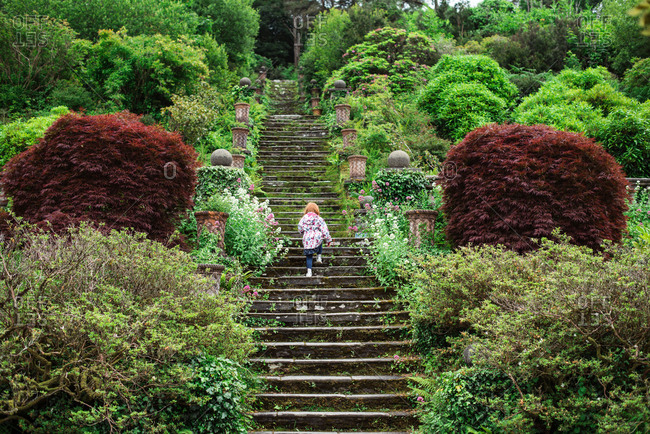 Girl climbing giant steps in a luscious garden in Ireland