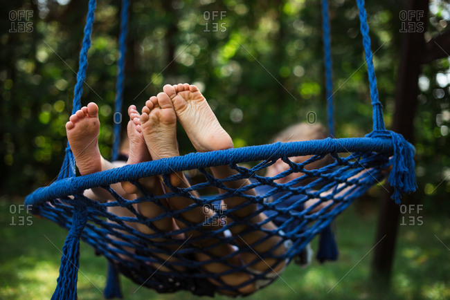 View of childrens feet on a garden swing