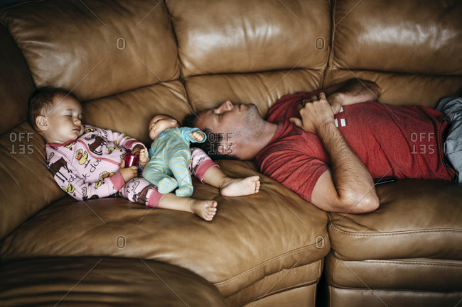 Girl and dad sleeping on couch