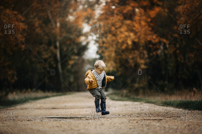 Boy jumping over puddle