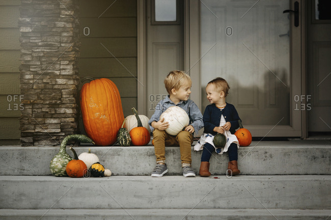 Boy and girl sit on porch with pumpkins
