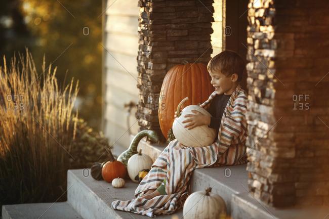 Boy holds pumpkin on porch
