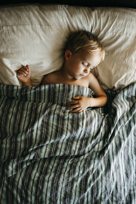 Boy sleeping with striped blanket