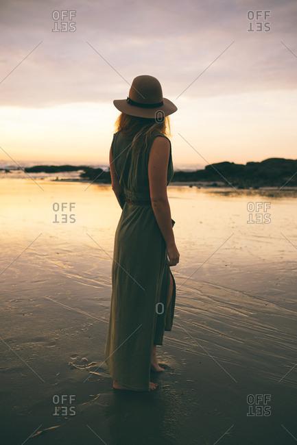 Woman in hat on dusky shore