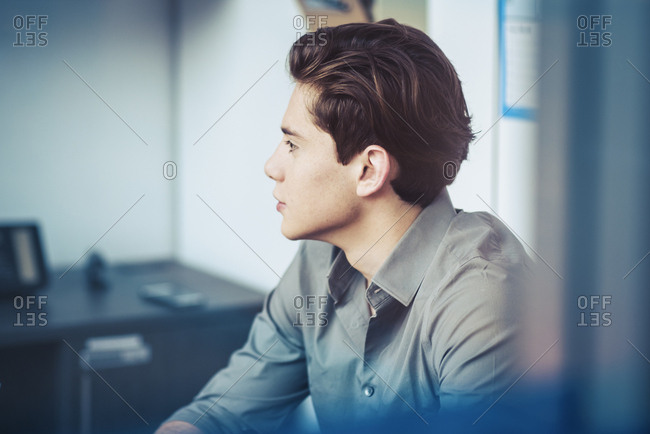 Young businessman looking away while sitting in office