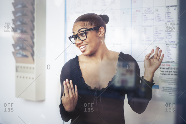 Mid adult businesswoman gesturing while giving presentation in office
