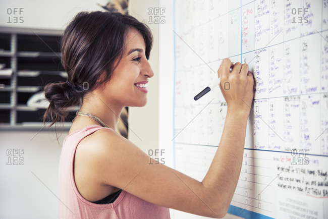 Confident smiling businesswoman writing reminders on calendar in office