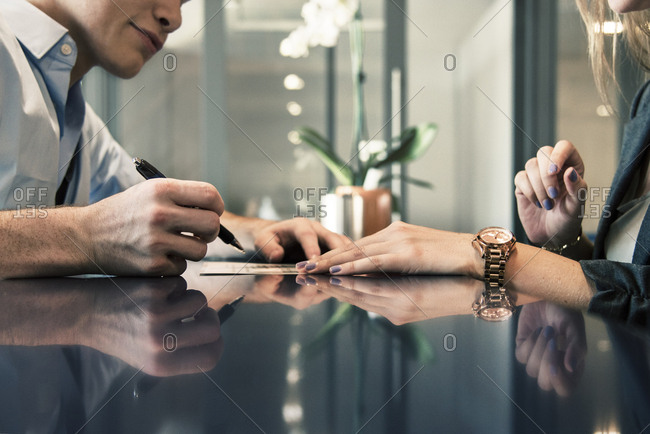 Cropped image of businessman filling form while female receptionist assisting him at counter in hotel