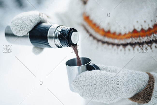 Woman in a knitted jumper and mittens drinks hot chocolate outdoors