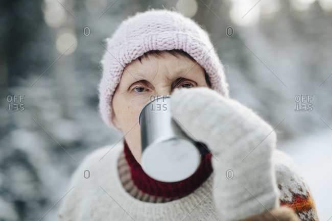 Grandmother drinking hot chocolate outdoors in a forest in Finland in winter