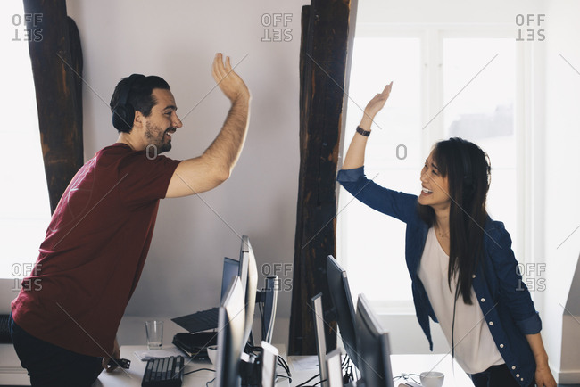 Smiling business colleagues giving high-five while standing by desk in office