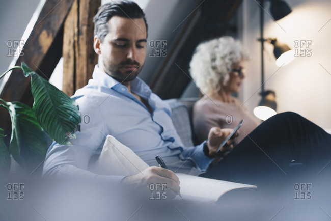 Businessman writing in diary while sitting by female colleague on sofa at office