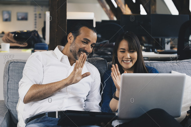 Smiling business colleagues waving at laptop during video conference at office