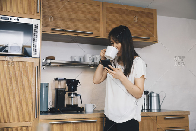 Mid adult businesswoman using mobile phone while drinking coffee from kettle at office