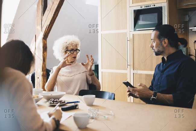 Senior businesswoman explaining to male colleague while sitting at table with breakfast in office