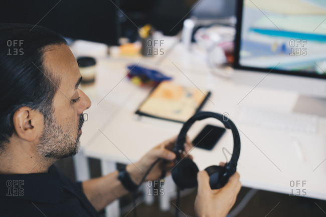 High angle view of mature businessman holding headphones at office
