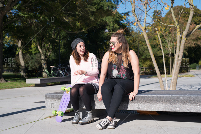 Two young women sitting on a bench laughing together