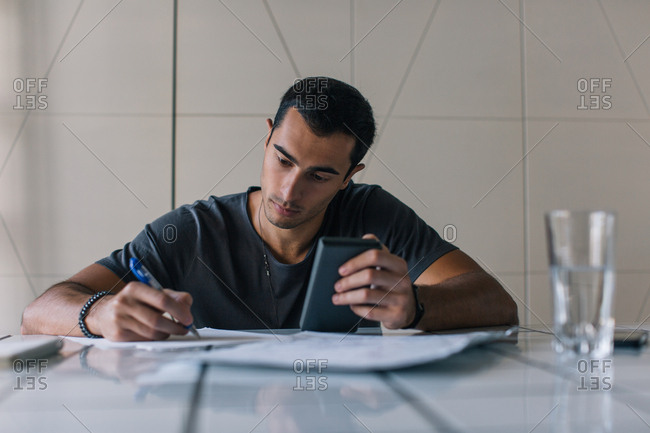 Young man holding a calculator and writing with pen and paper