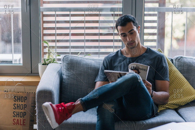 Man sitting on couch reading a magazine