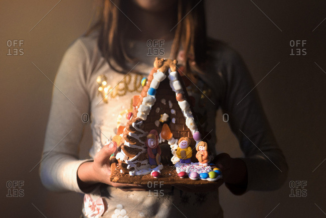 Girl holding a decorated gingerbread house