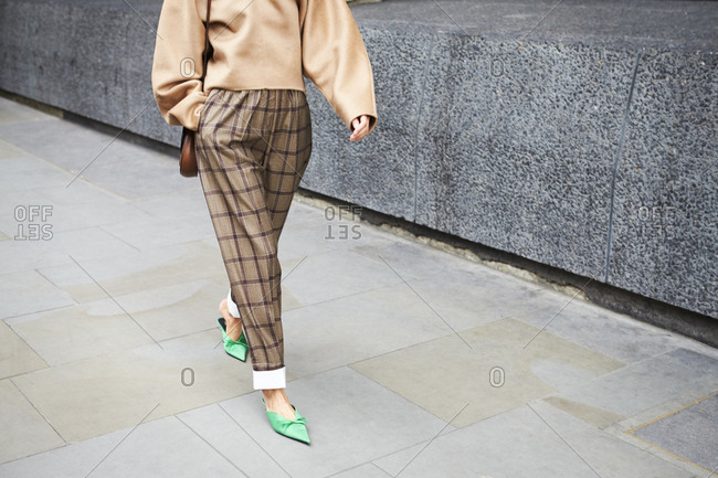 London - September 15, 2017: Woman in check trousers and green winklepicker shoes walking