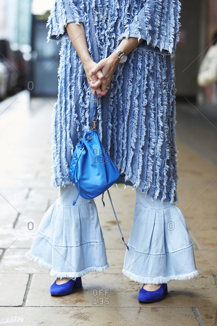 London - September 18, 2017: Low section of woman in blue frayed smock and bell bottoms