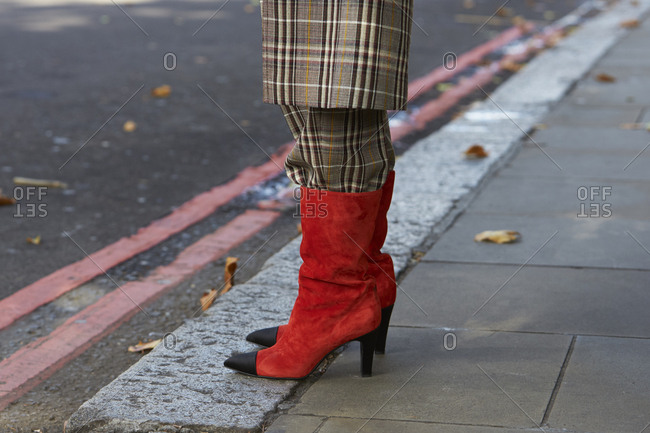 London - September 18, 2017: Woman in brown check coat and trousers tucked into red boots