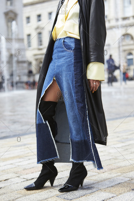 London - September 18, 2017: Woman in long denim skirt and leather coat, low section