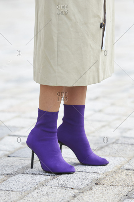 London - September 18, 2017: Low section of woman wearing mac and purple boots, vertical
