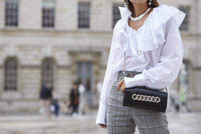 London - September 18, 2017: Woman in white frilled blouse holding bag, handbag, mid section