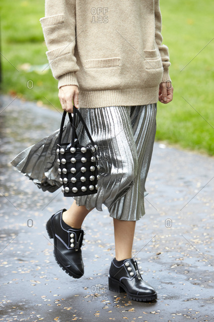 London - September 18, 2017: Woman wearing silver skirt carrying studded bucket bag