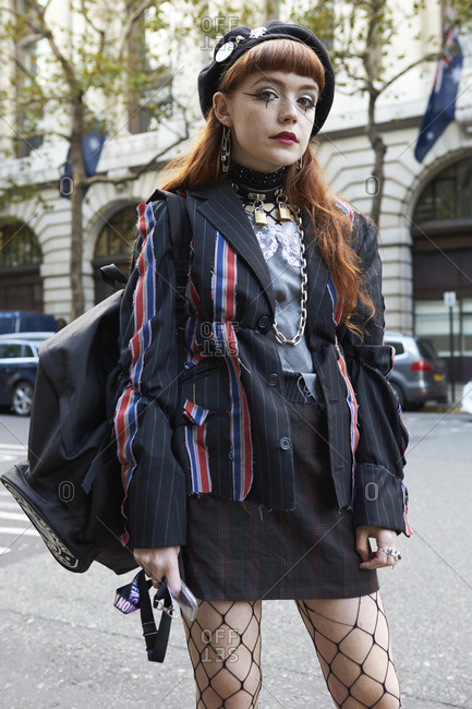 LONDON - 15 SEPTEMBER, 2017: Young woman wearing punk-inspired make-up and customized clothes standing in the street, Day 1, London Fashion Week.