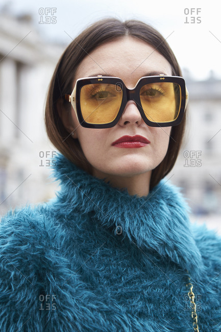 LONDON - 15 SEPTEMBER, 2017: Head and shoulders of woman wearing large Prada glasses and blue fake fur coat standing outside Somerset House, Day 1, London Fashion Week.