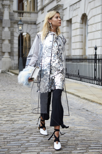 LONDON - 15 SEPTEMBER, 2017: Full length view of woman walking outside Somerset House wearing transparent coat over large-sequined dress and black trousers, with JW Anderson shoes, Day 1, London Fashion Week.