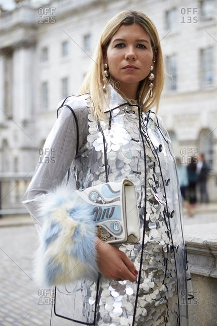LONDON - 15 SEPTEMBER, 2017: Woman outside Somerset House wearing transparent coat over large-sequined dress holding Miu Miu handbag Day 1, London Fashion Week.
