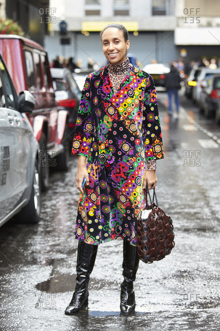 LONDON - 18 SEPTEMBER, 2017: Guest at LFW standing in the street wearing colorful patterned long velvet coat over leopard print top with know high black leather boots, Day 4, London Fashion Week.