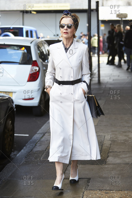 LONDON - 18 SEPTEMBER, 2017: LFW guest walking in the street wearing a long white double-breasted coat dress, correspondent high heeled shoes and sunglasses, Day 4, London Fashion Week.