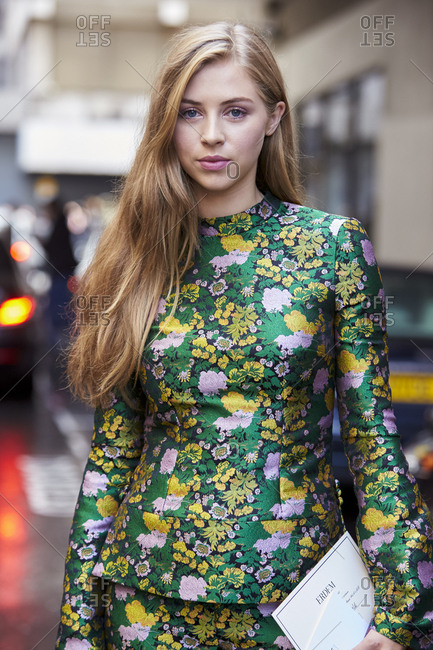 LONDON - 18 SEPTEMBER, 2017: Waist up portrait of actress Hermoine Corfield in the street wearing a green floral patterned silk trouser suit with a fitted top with band collar and flared sleeves, Day 4, London Fashion Week.