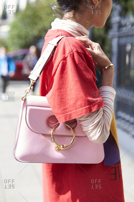 LONDON - 18 SEPTEMBER, 2017: Side view close up of fashion blogger Denni Elias in the street wearing oversized red t-shirt over long sleeved white turtleneck top, holding pink handbag, Day 4, London Fashion Week.