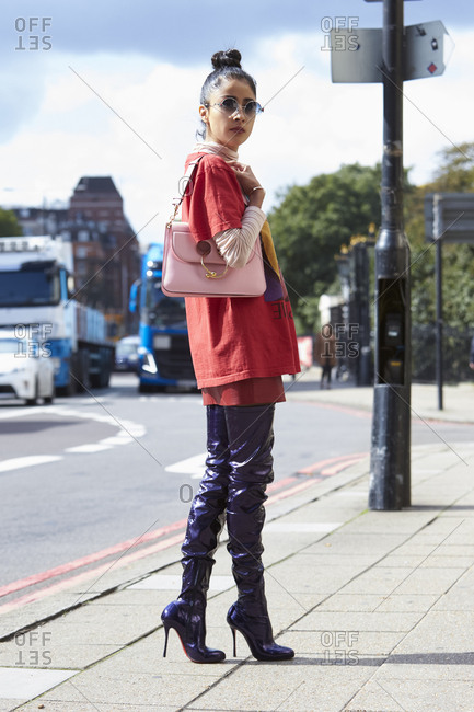 LONDON - 18 SEPTEMBER, 2017: Full length view of fashion blogger Denni Elias in the street wearing oversized red t-shirt over long sleeved white turtleneck top, red miniskirt and purple PVC trousers and high heeled boots, holding pink handbag, Day 4, London Fashion Week.