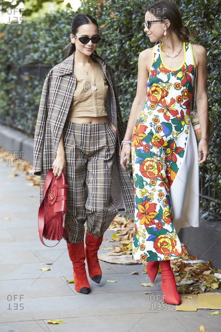 LONDON - 18 SEPTEMBER, 2017: Two women walking in the street together, one wearing checked trousers and coat and one wearing long white dress with floral print, both in red boots, Day 4, London Fashion Week.
