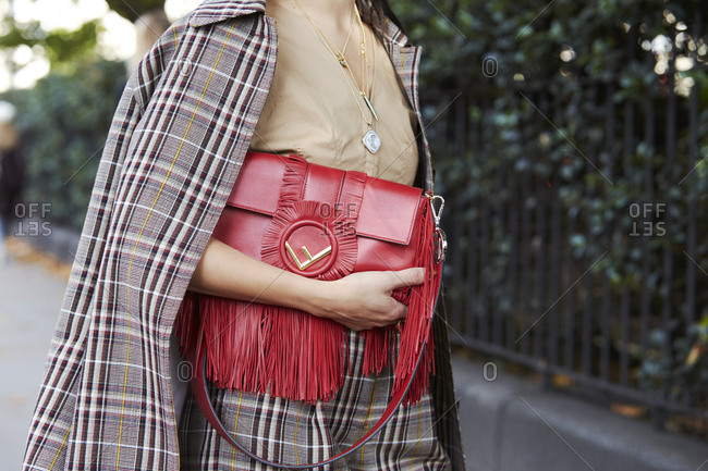 LONDON - 18 SEPTEMBER, 2017: Mid section of woman wearing checked coat and trousers holding fringed red leather Fendi handbag, Day 4, London Fashion Week.