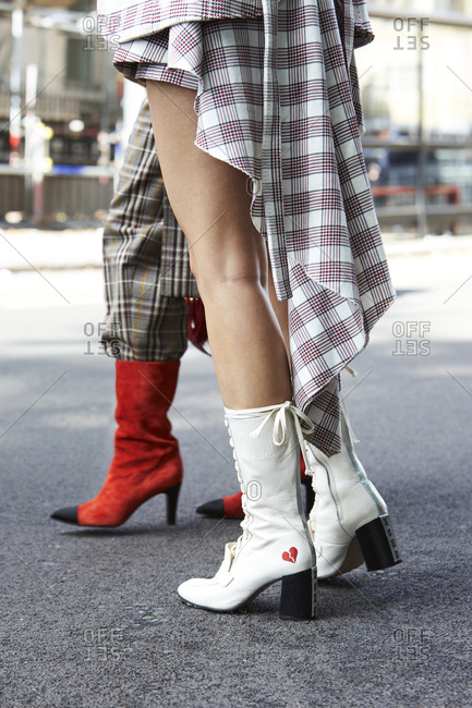 LONDON - 18 SEPTEMBER, 2017: Low section of two women standing on the street, one wearing white Havva boots and one in red suede Chanel boots, Day 4, London Fashion Week.