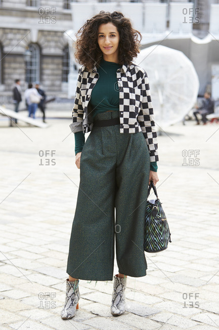LONDON - 18 SEPTEMBER, 2017: Guest at LFW standing outside Somerset House wearing short black and white check jacket over long sleeved dark green top and culottes with snakeskin ankle boots, Day 4, London Fashion Week.