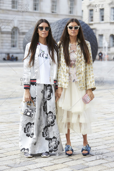 LONDON - 18 SEPTEMBER, 2017: Two sisters standing outside Somerset House wearing sunglasses, one in silver baseball jacket and floor-length skirt, one in patterned jacket and cream tulle layered dress, Day 4, London Fashion Week.