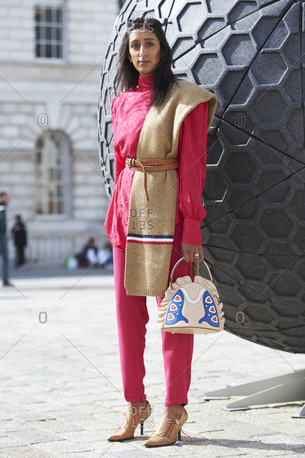 LONDON - 18 SEPTEMBER, 2017: Fashion Blogger Nikita Chandni wearing red trousers and belted red silk blouse with a wool shawl over one shoulder and lace up stiletto shoes, holding a leather appliqu� handbag, Day 4, London Fashion Week.