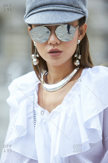LONDON - 18 SEPTEMBER, 2017: Portrait of woman wearing grey cap, mirror sunglasses and white blouse with frill at the neck, Day 4, London Fashion Week.