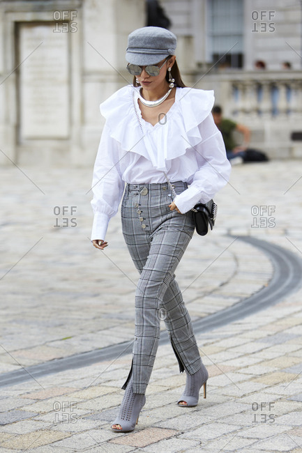 LONDON - 18 SEPTEMBER, 2017: Woman wearing grey checked trousers with white blouse, grey cap and high heels walking in front of Somerset House, Day 4, London Fashion Week.