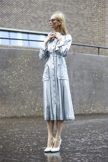 LONDON - 18 SEPTEMBER, 2017: Full length view of woman standing in the street wearing a long silver shirt waist dress with bib front and bow collar, Day 4, London Fashion Week.