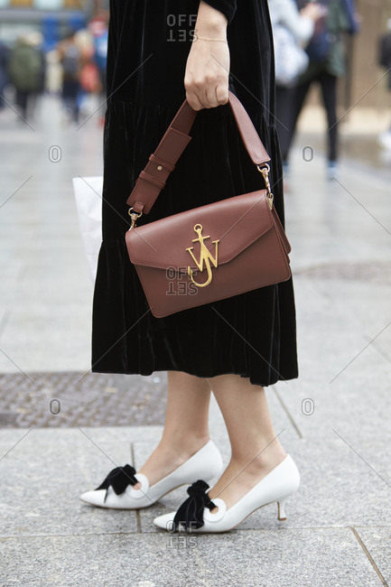 LONDON - 18 SEPTEMBER, 2017: Low section of woman wearing long black dress and white kitten heel shoes holding a brown leather JW Anderson handbag, Day 4, London Fashion Week.